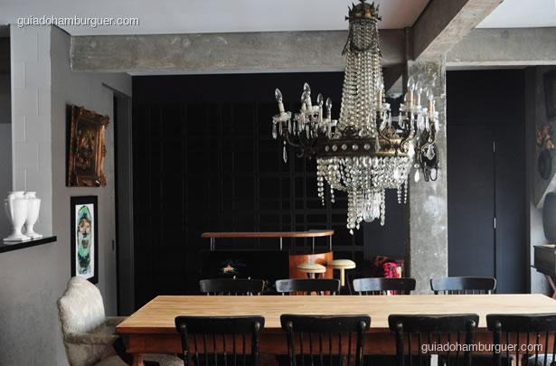 Salão com grande lustre e mesa para dez pessoas