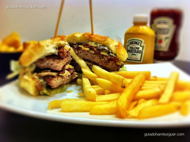 O lanche é preparadao com 2 hambúrgueres, leva champignon, shiitake salteado, alecrim, bacon, maionese de alho, alface, pão de gergelim