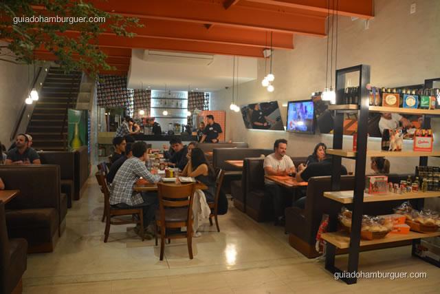 Ambiente com os sofás na laterais e mesas ao centro - Burger Lab Experience
