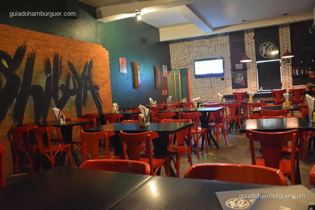 Ambiente espaçoso com mesas e cadeiras vermelhas - Hamburgueria 162 Station