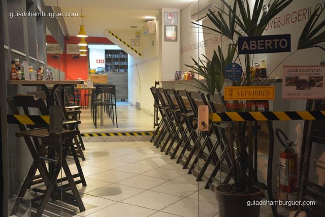 Porta de entrada com balcão à direita e mesas ao fundo - I Love Burger