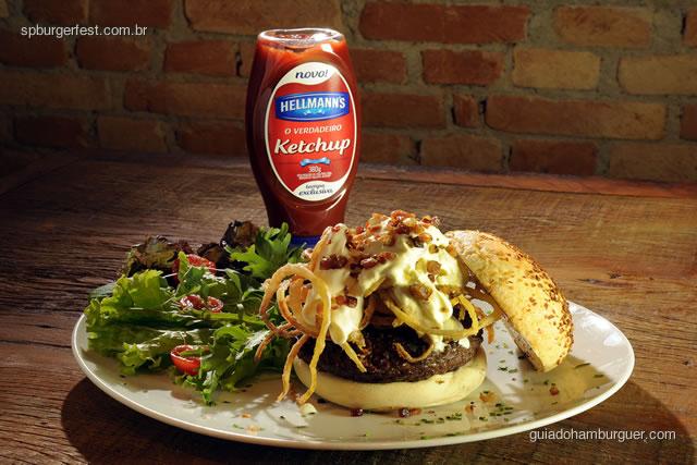 Vincent Vega - hambúrguer de 250 gramas recheado de muçarela e bacon, coberto por sour cream salpicado de bacon bits e crispy onions, servido no pão de cebola. Acompanha salada no prato. - SP Burger Fest 3ª edição