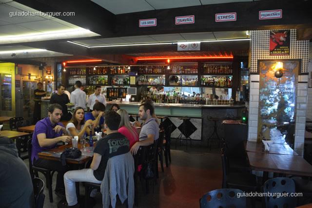 Ambiente com o bar ao fundo - La Maison Est Tombeé