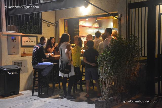 Entrada bem cheia, a espera pode ser feita na porta ou em mesas e cadeiras em frente - Na Garagem Hamburgueria Artesanal