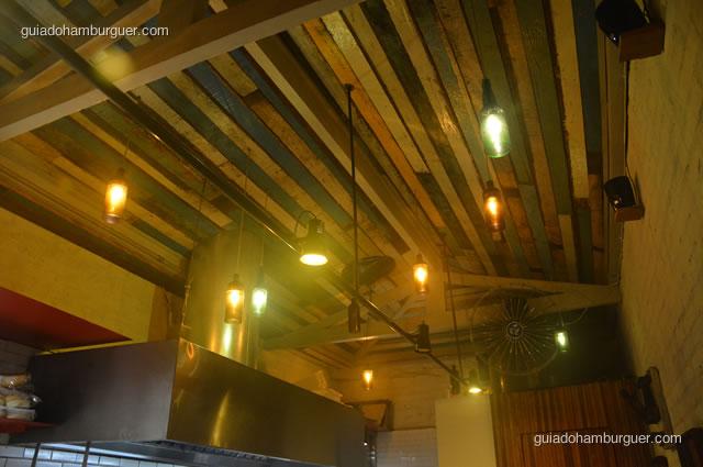 O teto é alto e iluminado, a decoração foi feita nos mínimos detalhes - Na Garagem Hamburgueria Artesanal