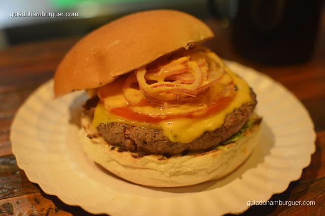 Detalhes dos ingredientes: hambúrguer de 130g, queijo, alface, tomate, ceola roxa e o molho exclusivo de cenoura - Na Garagem Hamburgueria Artesanal