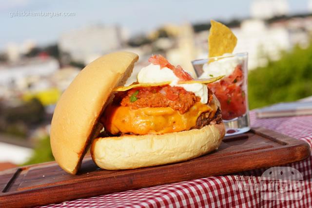 Hambúrguer artesanal de 180g de fraldinha, queijo cheddar, chilli levemente apimentado, pico de gallo , sour cream e nachos crocantes no pão de cebola. - Butantan Food Park