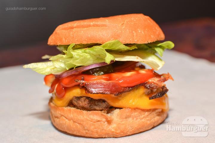 Bacon Works, hambúrguer de 140g, queijo colby e cheddar, bacon, alface, tomate, cebola roxa, picles, ketchup, maionese e mostarda por R$ 25,00 - Por trás das cortinas vermelhas do Burger Joint