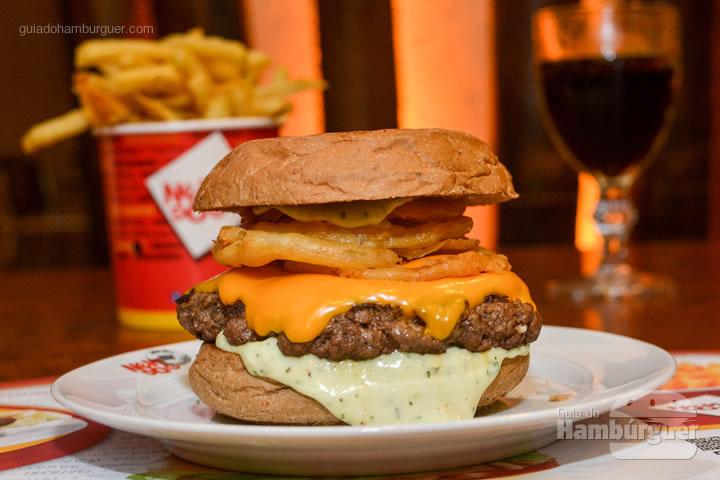 Black Aust, hambúrguer de 200g, queijo cheddar, onion rings e maionese New Dog com um toque de manjericão no pão australiano que custa R$ 39,00 - New Dog no Burger Fest