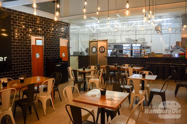 Vidraça ao fundo que separa a cozinha do ambiente dos clientes - Burger Shop