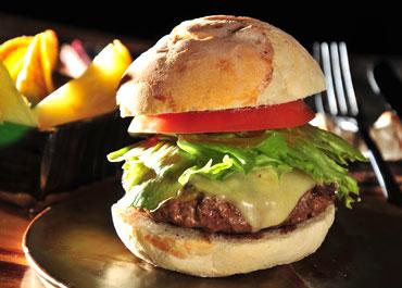 Burger da Casa, com carne de 200g, levemente defumado no prato e servido com queijo Serra da Canastra derretido, relish de tomates assados, bacon e fritas rústicas por R$ 28,00 - Rothko Restaurante